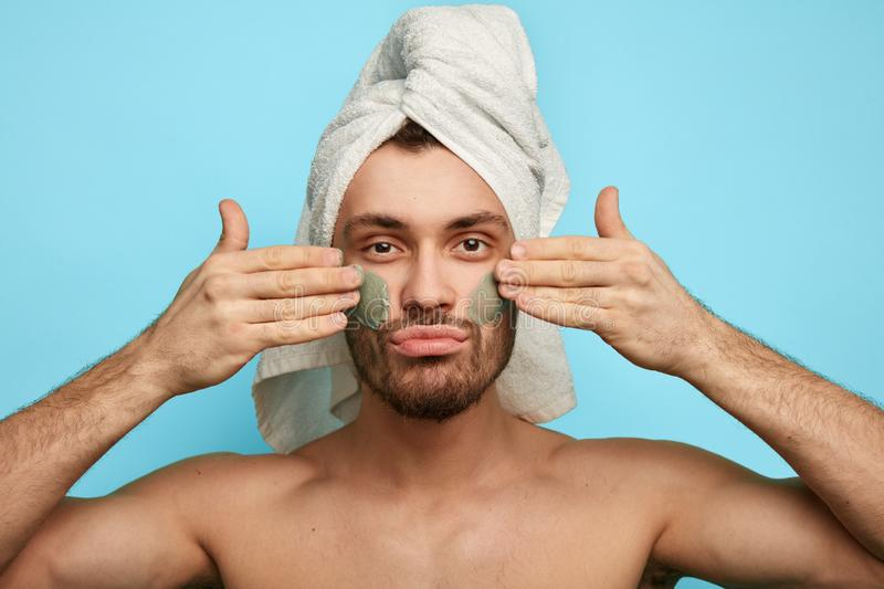 Young man with anti aging cream on the face. royalty free stock photography
