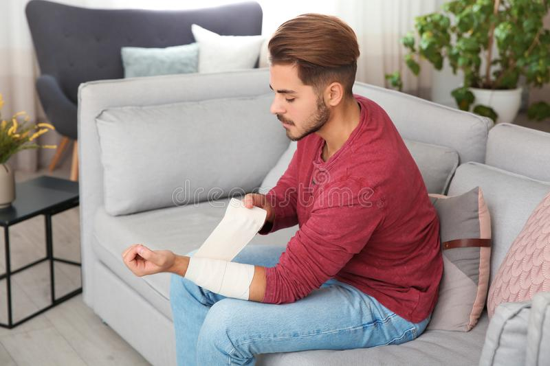 Young man applying bandage on injured arm at home. stock image
