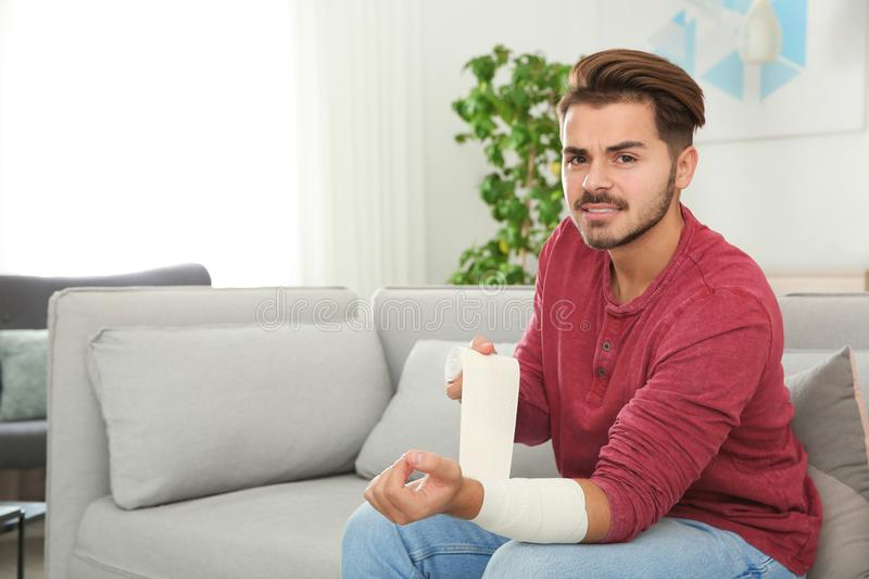 Young man applying bandage on injured arm at home, space for text royalty free stock photo