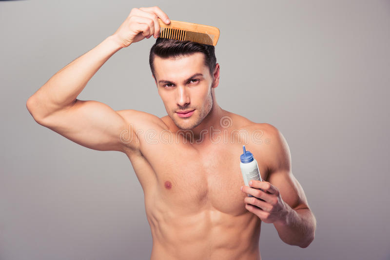 Young man applying hair spray to his hair. Over gray background. Looking at camera stock photos