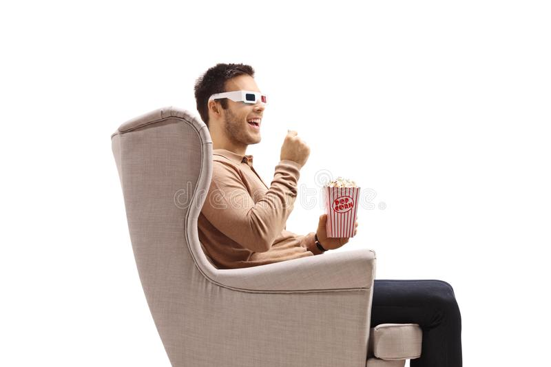Young man in an armchair wearing a pair of 3D glasses and eating popcorn royalty free stock images