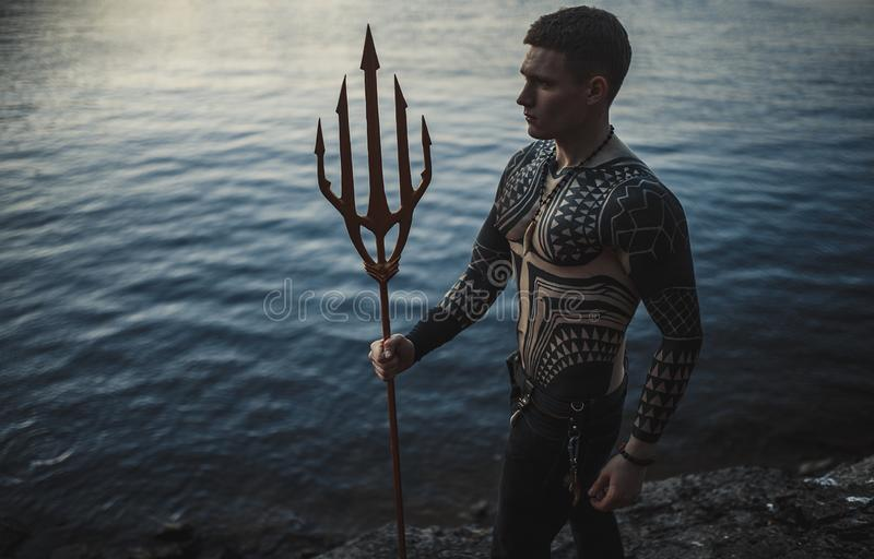 A young man with a trident against the background of water. A young man in armor with a trident in his hands against the background of water royalty free stock photography