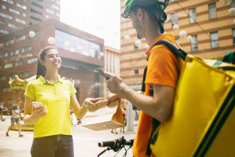 Young man as a courier delivering package using gadgets. Young men in yellow shirt delivering package using gadgets to track order at the city`s street. Courier royalty free stock photos