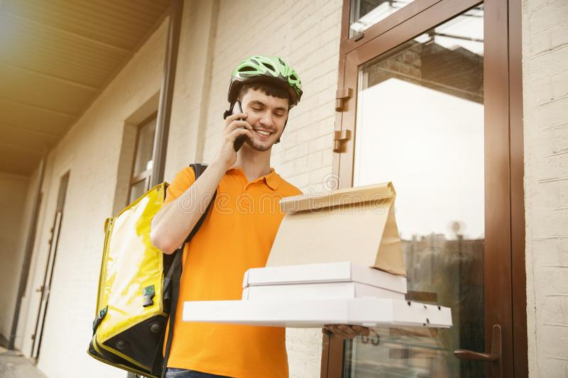 Young man as a courier delivering pizza using gadgets. Young man in yellow shirt delivering pizza using gadgets to track order at the city`s street. Courier stock photography
