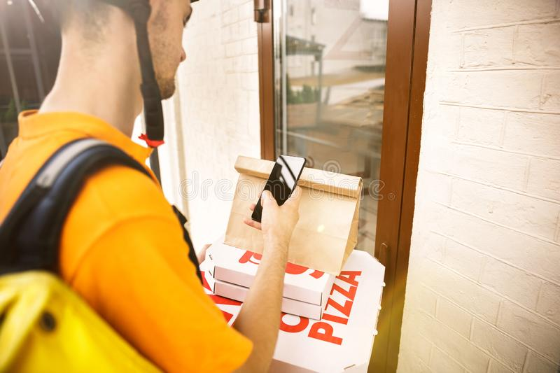 Young man as a courier delivering pizza using gadgets. Young man in yellow shirt delivering pizza using gadgets to track order at the city`s street. Courier stock image