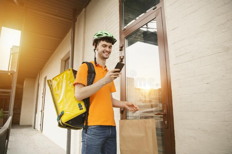 Young man as a courier delivering pizza using gadgets. Young man in yellow shirt delivering pizza using gadgets to track order at the city`s street. Courier royalty free stock images