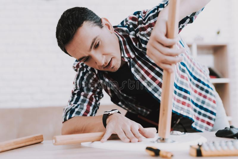 Young Man Assembling Coffee Table and Stools royalty free stock images