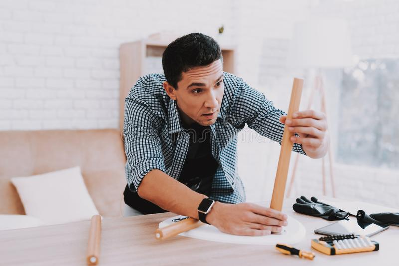 Young Man Assembling Coffee Table and Stools royalty free stock photos
