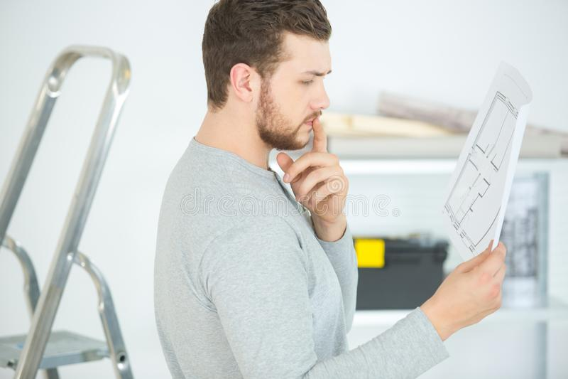 Young man assembling flatpack closet at home reading manual. Man royalty free stock images