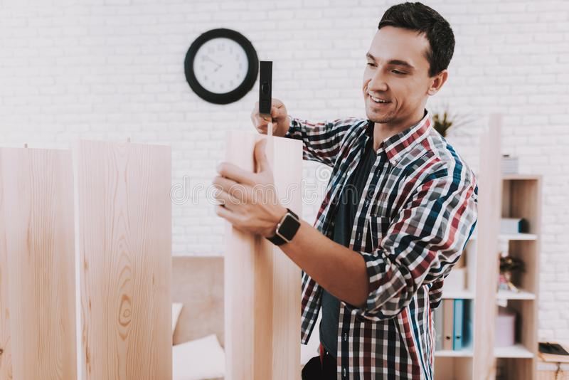 Young Man Assembling Wooden Bookshelf at Home. stock image