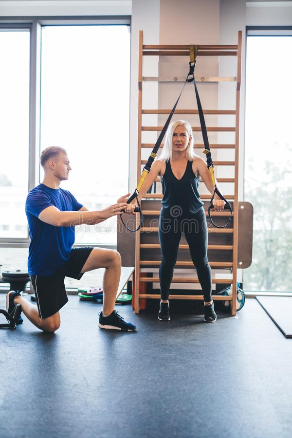 Young man assisting an exercising woman. stock image