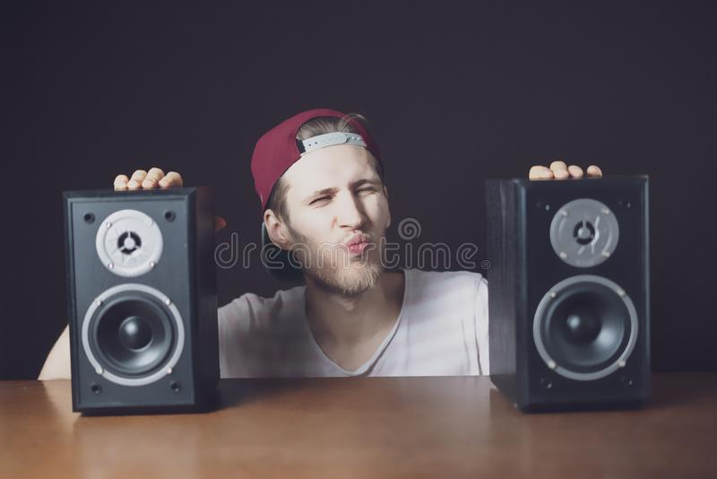 Young man audiophile listen to loud music from speakers f royalty free stock photos