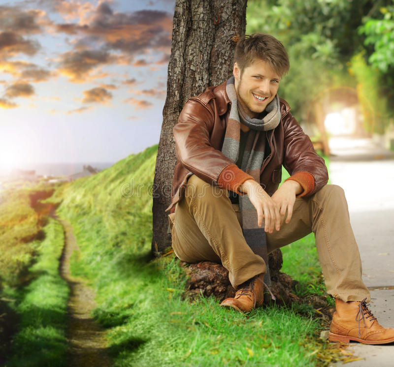 Young man in autumn. Young stylish happy man in autumn clothing leaning against tree next two path fading off in the distance stock photos