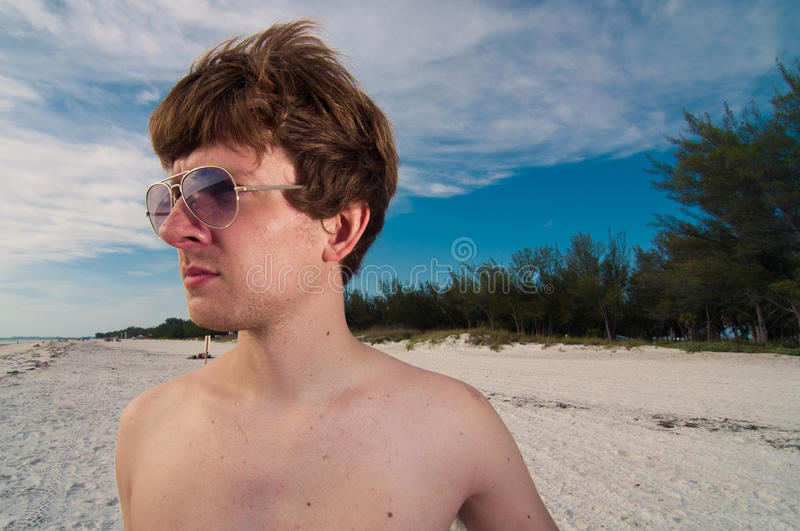 Young Man with Aviators at the Beach.  royalty free stock image