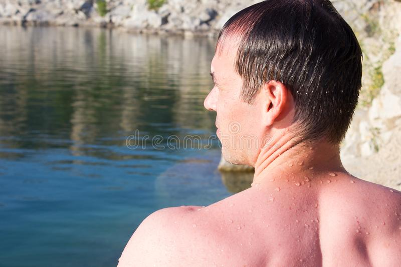 Young man on a background stones, water - summer sunny sea stock photo