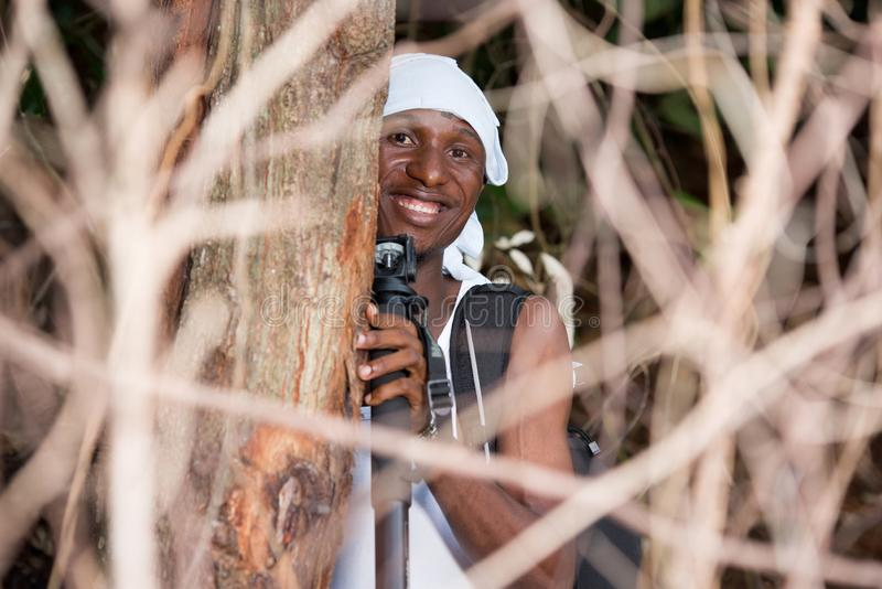 Close-up of young man in the countryside, happy. Young man backpack with head tied up standing in bush looking at camera smiling royalty free stock images