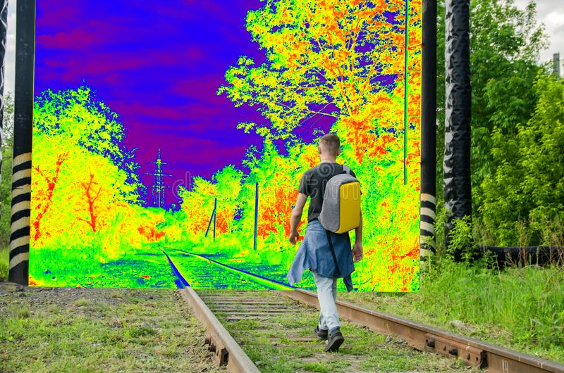 Young man with a backpack on his back goes forward along an abandoned railway to a psychedelic other world. concept of decisive stock image