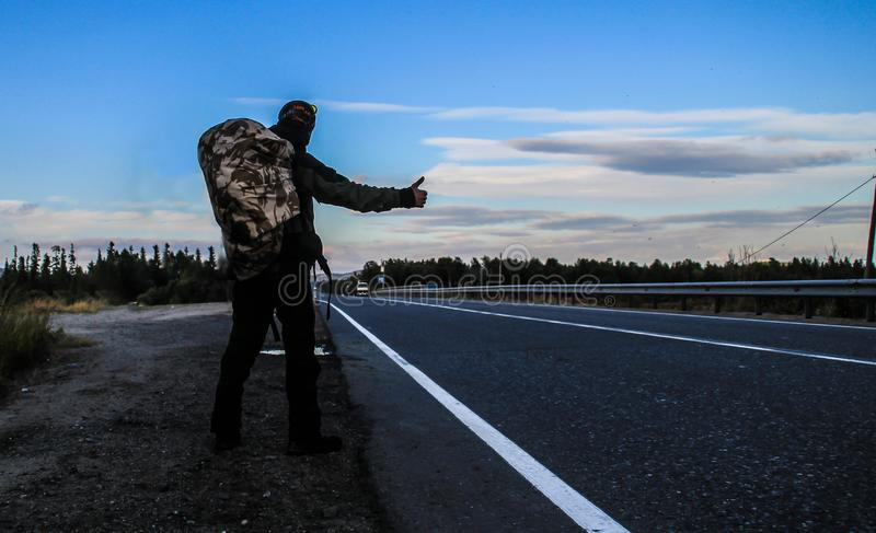 A young man with a backpack hitchhiking and waiting for a car on the highway late in the evening. At dusk royalty free stock images