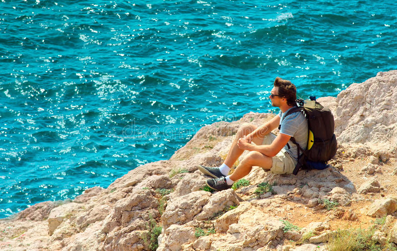 Young Man with backpack relaxing on rocky cliff with blue Sea on background stock photography