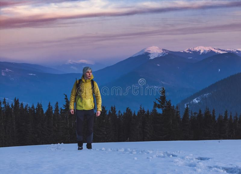 Young man with backpack standing on the snow and looking aside with beautiful mountains on the background.  royalty free stock photos