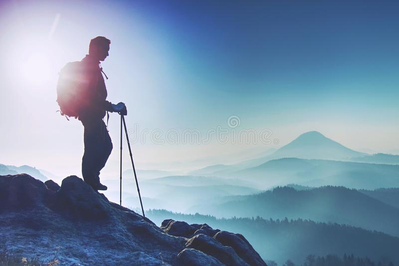 Young man with backpack standing on top of mountain and enjoying mountain view. Hiker on the mountain top. Sport and active life stock image