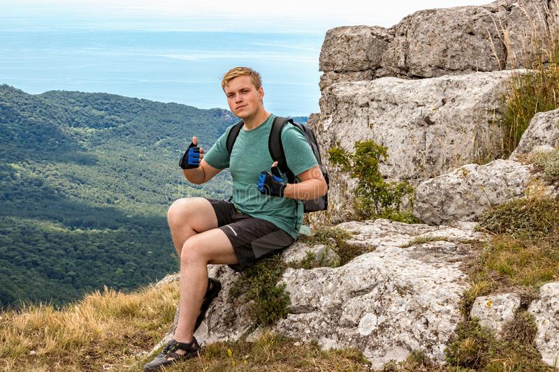 Young man with a backpack on top of cliff enjoying view of nature. Mountains and sea stock photo