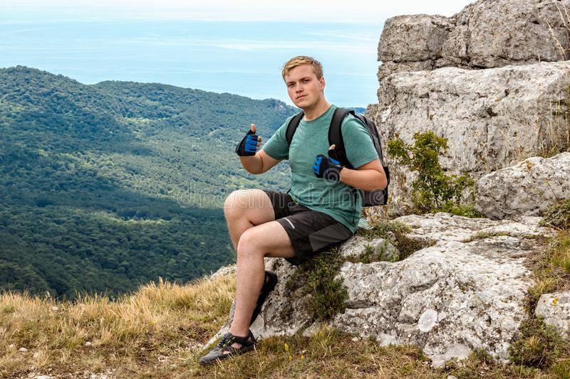 Young man with a backpack on top of cliff enjoying view of nature. Mountains and sea stock photos