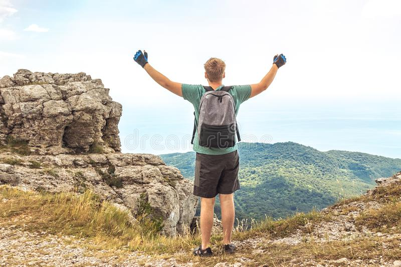 Young man with a backpack on top of cliff enjoying view of nature. Mountains and sea stock photography