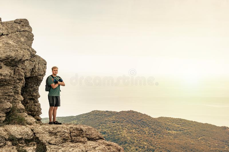 Young man with a backpack on top of cliff enjoying view of nature. Mountains and sea royalty free stock photo