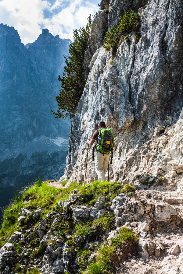 Young man backpacker walking on mountain trail Cinque Torri, Cor stock images