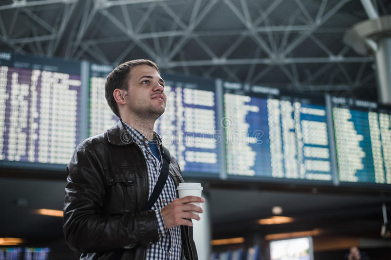 Young man with a bag in airport near flight timetable holding cup of coffee royalty free stock photos