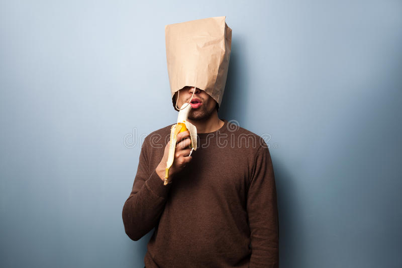 Young man with bag over head eating banana. Young man with a bag over his head is eating a banana royalty free stock photo