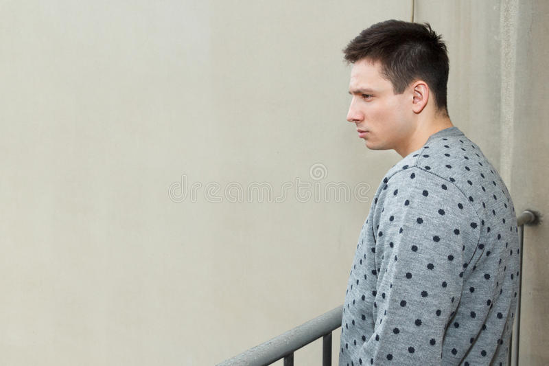 Young man at balcony in depression sufferin. G emotional crisis. Attractive male model looking down from balcony. Person on terrace looks to somber and desolate stock images