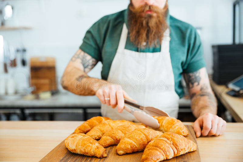 Young man barista with beard taking croissant using tongs royalty free stock image