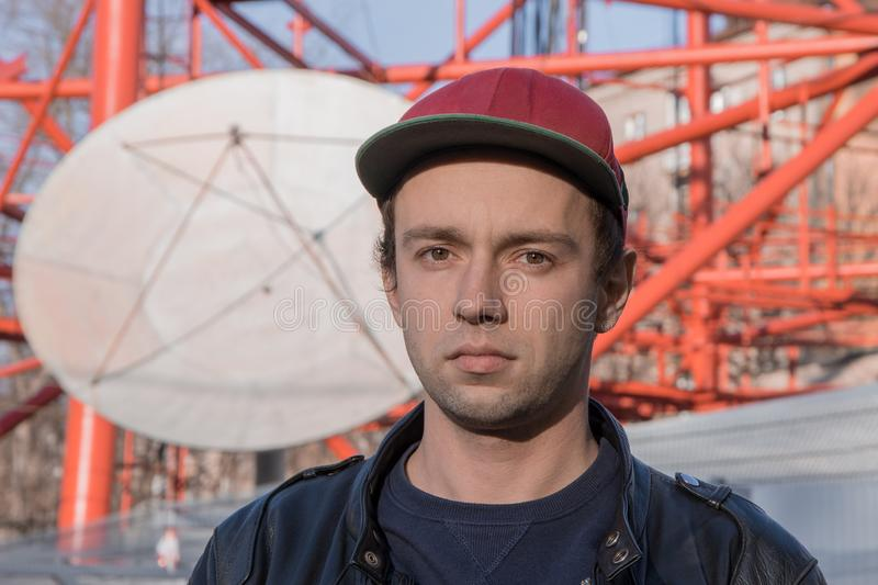 A young man in a baseball cap looks directly into the camera against the background of a satellite dish and a construction royalty free stock photos