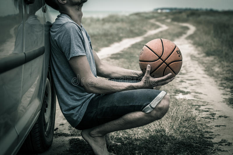 Young man with basketball ball on the road, the emotions of the athlete stock photo