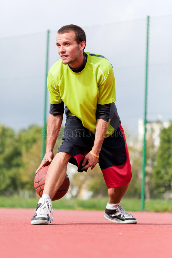Young man on basketball court dribbling with ball. Streetball, training, activity. Real and authentic stock photography