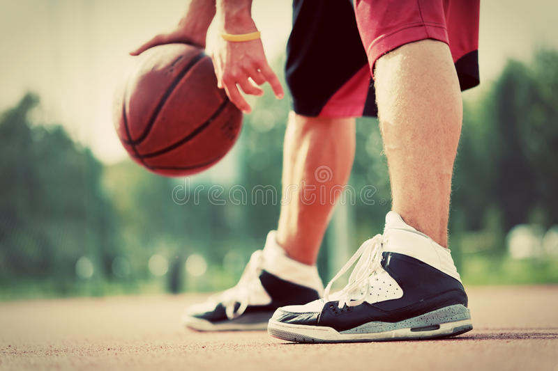 Young man on basketball court dribbling with ball. Streetball, training, activity. Real and authentic, vintage mood stock photography