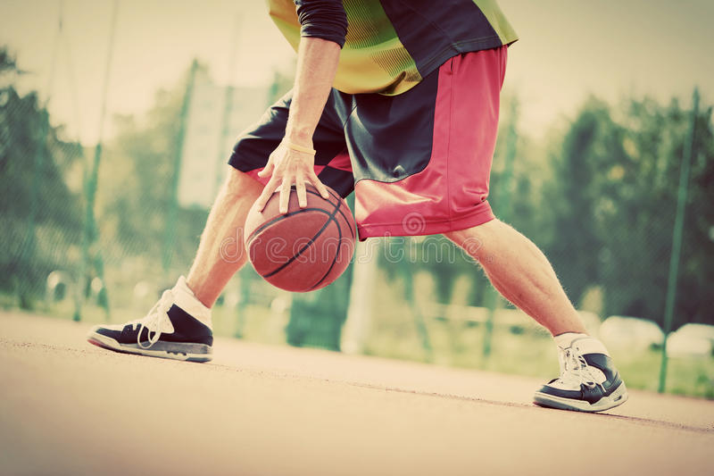 Young man on basketball court dribbling with ball. Vintage. Young man on basketball court dribbling with ball. Streetball, training, activity. Real and authentic stock photo