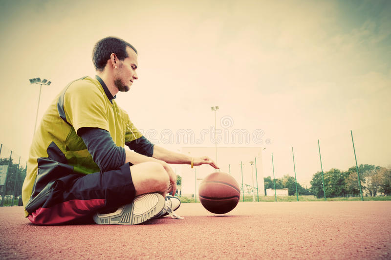 Young man on basketball court. Sitting and dribbling. With ball. Streetball, training, activity. Real and authentic, vintage mood royalty free stock photography