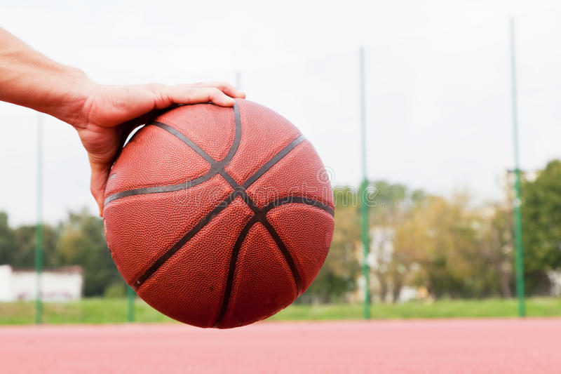 Young man on basketball court. Sitting and dribbling with ball. Dribbling the ball on basketball court. Streetball, training, sport. Real and authentic royalty free stock photography