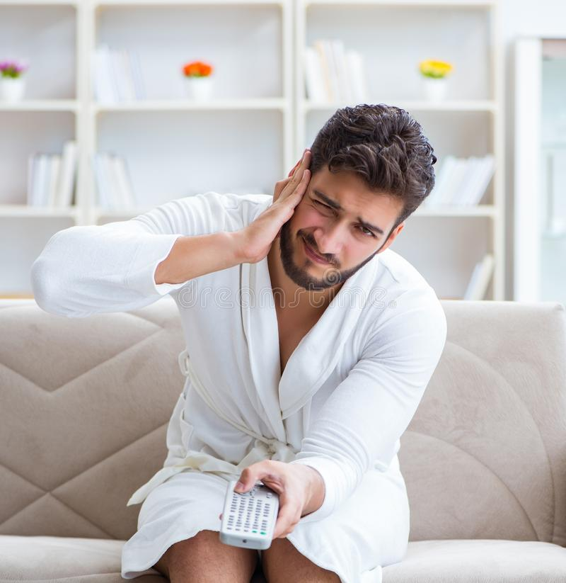 Young man in a bathrobe watching television at home on a sofa co stock photos
