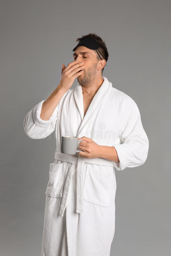 Young man in bathrobe yawning on background royalty free stock photos