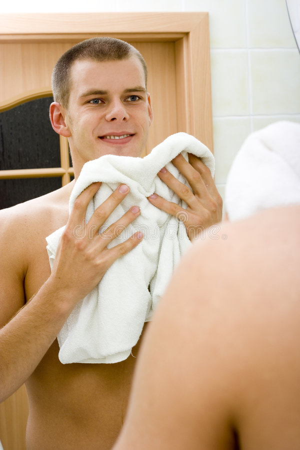 Young man in the bathroom's mirror after shave royalty free stock photography