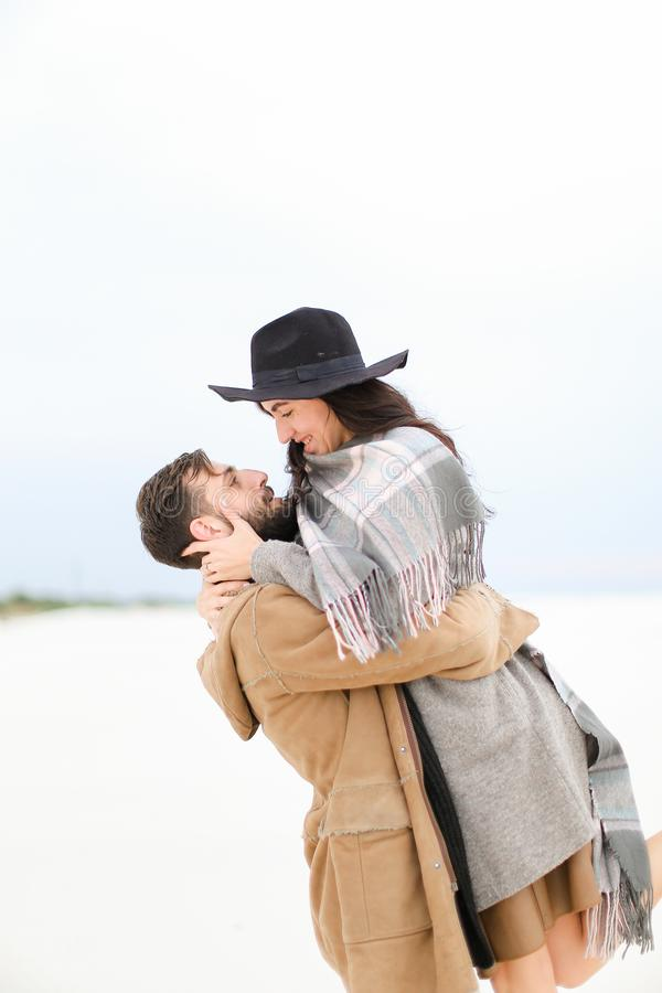 Young man with beard picking up young woman wearing hat, coat and grey scarf on white snow background. Young men with beard picking up young women wearing hat stock images