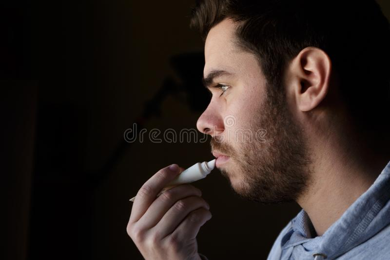 Young man with a beard repairing his damaged lips with moisturizer royalty free stock photos