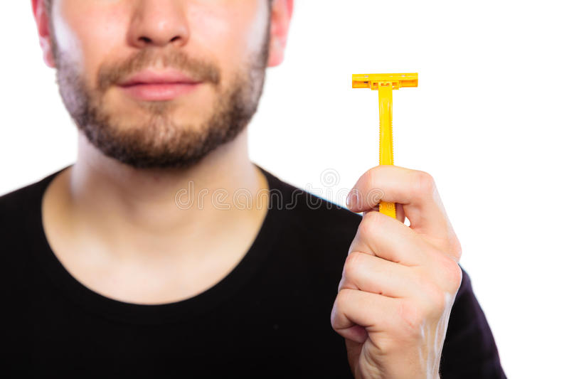 Young man with beard showing razor blade royalty free stock image