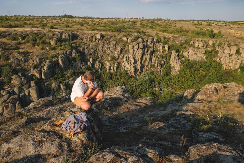 Young man with a beard sitting on canyon cliff royalty free stock photos