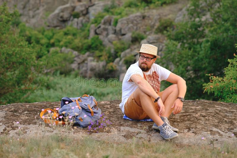 Young man with a beard sitting on canyon cliff stock photos