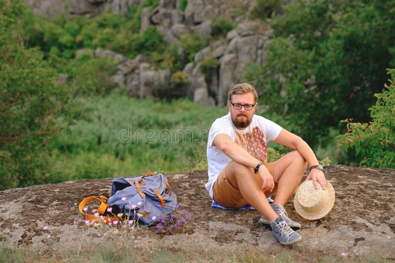 Young man with a beard sitting on canyon cliff royalty free stock images